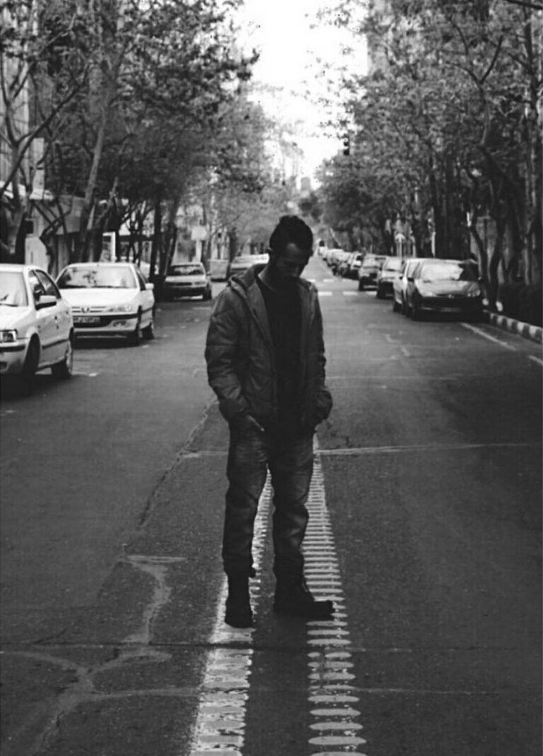 Nikan Khosravi står midt i gata med hendene i lomma og ser ned.