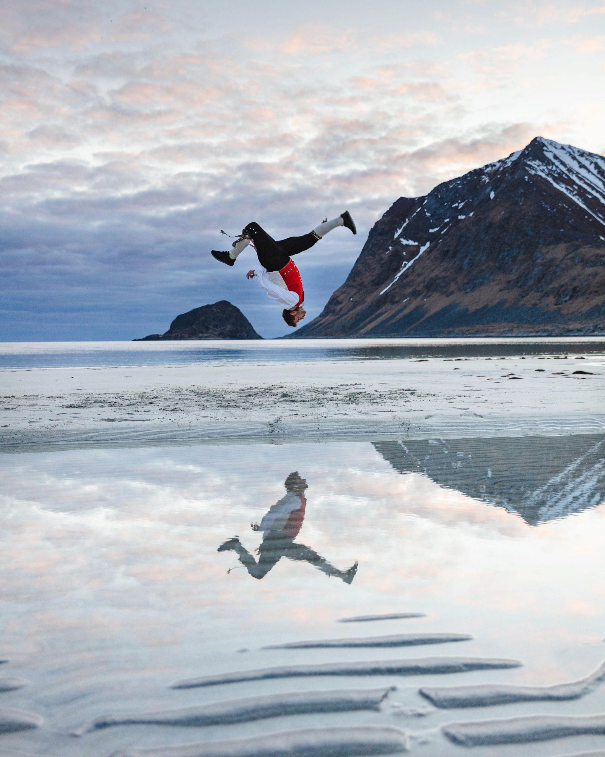 Daniel Grindeland i bunad med fjell i bakgrunnen - han hopper opp-ned
