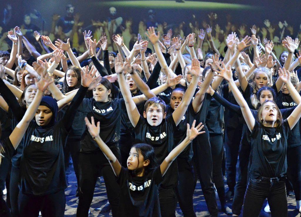 Barn med svarte t-skjorter strekker armene i været på scenen.