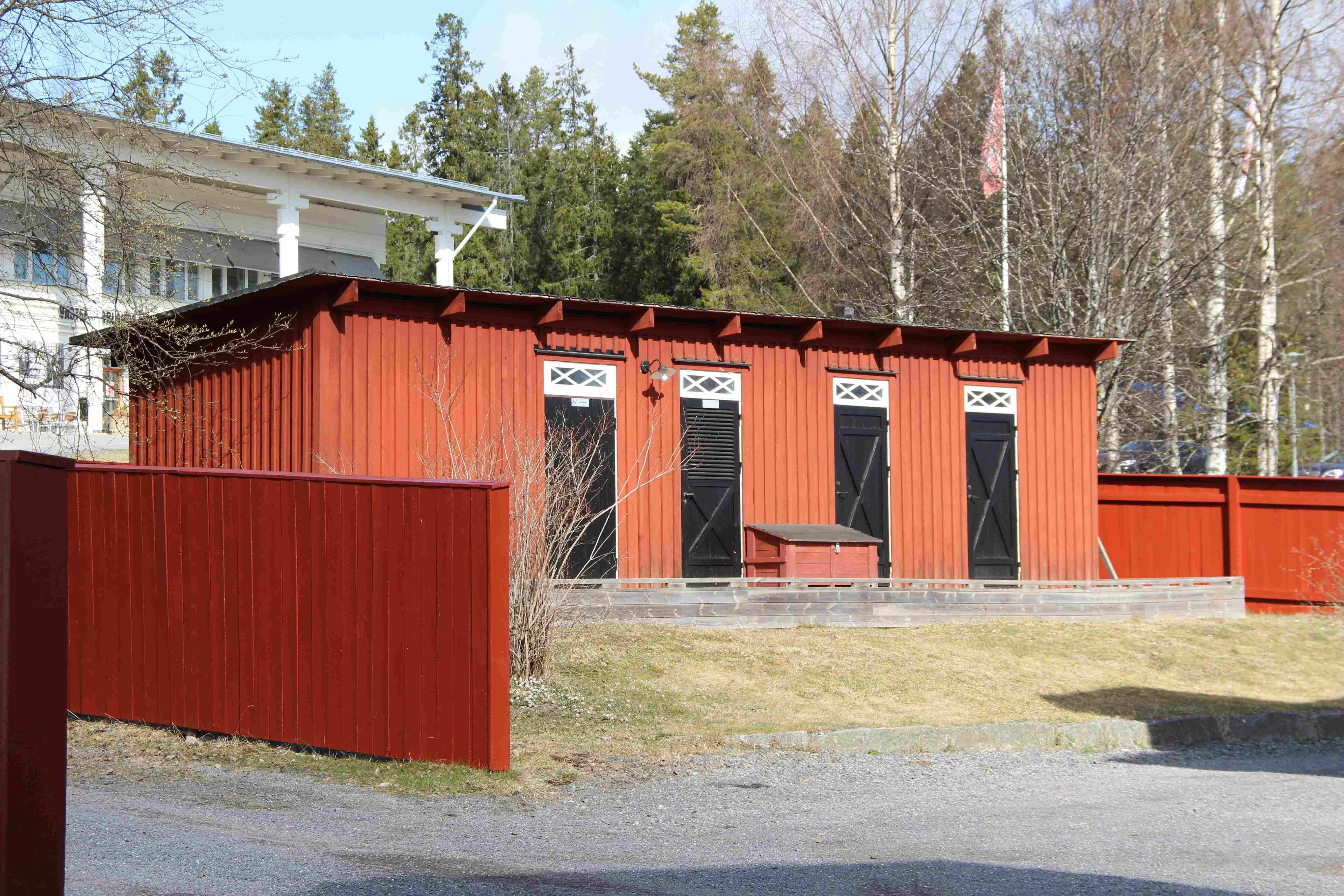 Dasslängan bakom Hellströmska huset är en rödmålad byggnad med fyra svarta dörrar med vita överljus. Taket är ett pappklätt pulpettak. Byggnaden omges av röda plank. I bakgrunden skymtar museibyggnaden.