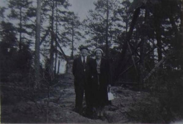 ett svartvit fotografi på en man och en kvinna framför träd