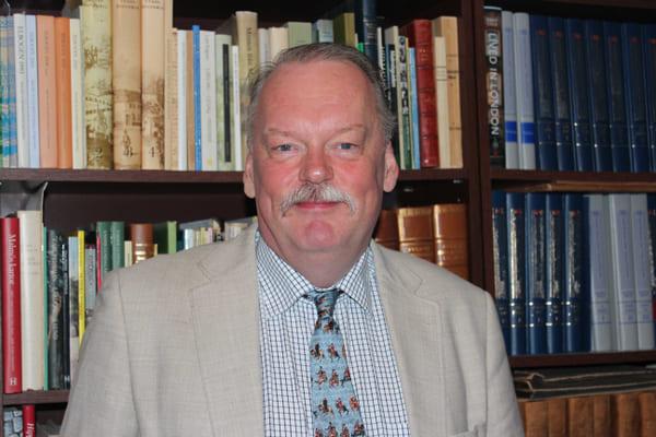 Ett porträttfoto på en man som står framför en bokhylla full med böcker. Mannen är klädd i ljus kostym och slips.