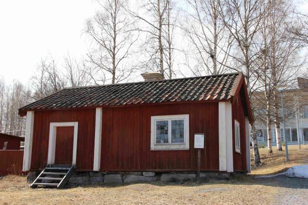 en röd timrad stuga med tegeltak och ett fönster med många spröjs