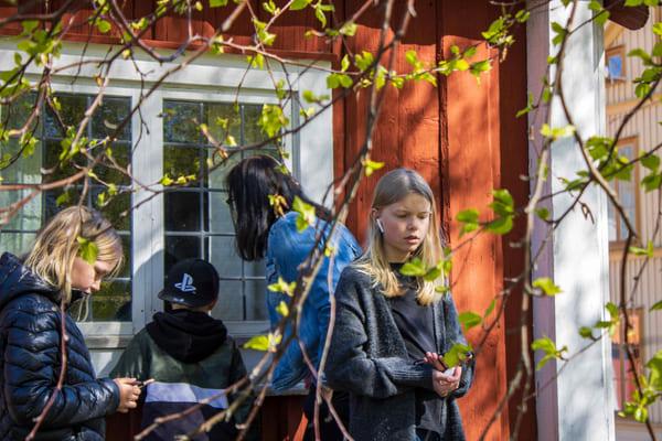 tre barn och en vuxen person framför ett rött timrat hus. de har hörlurar och lyssnar på berättelser