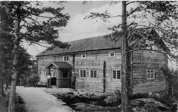 en svartvit bild på ett gammalt timmerhus