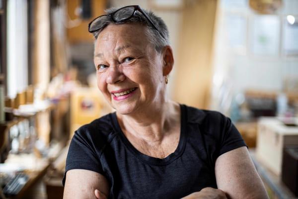 Poträttfoto på en kvinna i kortklippt hår, glasögon, svart t-shirt och guldörhängen. Hon står inne i en verkstad.