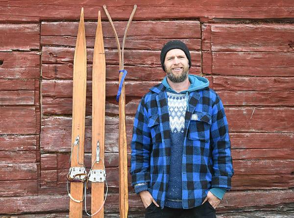 en man i rutig jacka står bredvid ett par skidor. I bakgrunden en röd timmervägg
